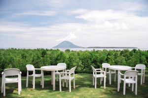 Plastic tables and chairs, mangrove trees and Bunaken island
