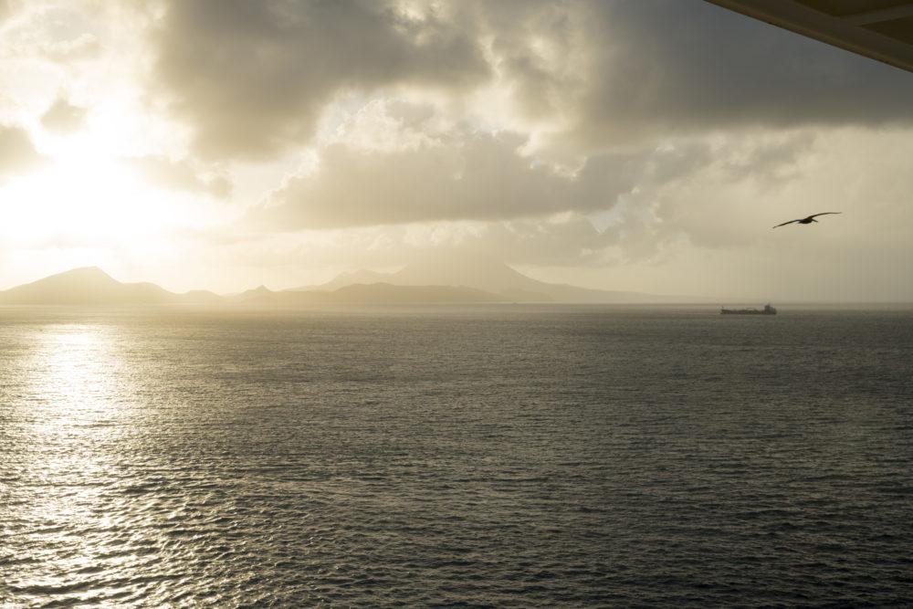 sun shining behind island